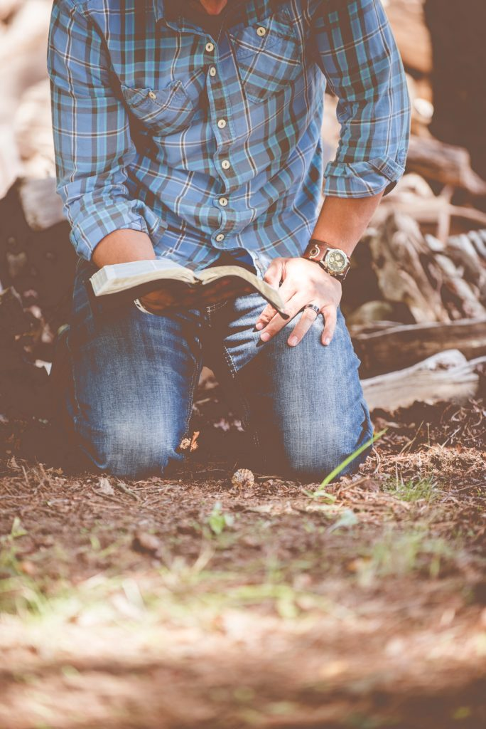 man-kneeling-reading-bible